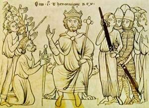 """Ottos Sieg über Berengar II.: Otto I. (""""Thevconicor(um) REX"""") empfängt als Zeichen der Unterwerfung ein Schwert vom links knienden König, der mit """"Beringarius"""" bezeichnet wird. Der Gefolgsmann Ottos rechts trägt ein Schwert mit der Spitze nach oben als Zeichen der Richtgewalt. Illustration einer Handschrift der Weltchronik Ottos von Freising (Mailand, Biblioteca Ambrosiana, Cod. S.P.48, olim F 129 Sup.), um 1200. Quelle: Wikipedia"""